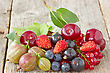 Pile Of Assorted Berries On The Wooden Floor stock photography