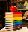 Pile Of Colorful Books With An Apple On It