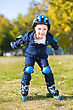 Playful Little Boy Riding On Roller Skates And Smiling stock photo