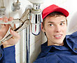 Plumber In Uniform Repairing Old Pipe In The House.
