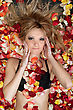 Portrait Of Attractive Blonde Lying In Rose Petals stock photo
