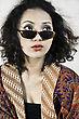 Cloth Portrait of a beautiful woman with curly hair wearing traditional dress and wearing sunglasses in the studio. stock photography