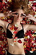 Portrait Of Beautiful Young Woman Lying In Rose Petals stock photo