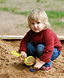 Portrait Of A Child - A Little Girl Playing With Sand stock photo