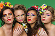 Portrait Of Four Young Beautiful Girls Wearing Flower Accessories Over Green Background stock image