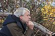 Portrait Of Mature Thoughtful Man With Grey Hair In Forest In Autumn Day