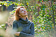 Smiling Portrait Of Red-haired Adult Woman In Nature stock photo