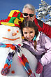Skiing Portrait Of A Senior Man And A Little Girl With Snowman stock photo