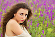 Portrait Of Sexy Curly Brunette Posing In A Flowering Field stock photography