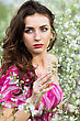 Portrait Of Thoughtful Nice Brunette Posing In Flowering Trees stock photo