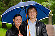 Portrait Of Young Couple Under Umbrella In The Park stock photo