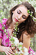 Portrait Of Young Curly Lady Touching The Branch Of Flowering Tree stock photo