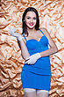 Portrait Of Young Smiling Brunette Posing In Blue Dress And White Gloves
