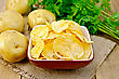 Potato Chips In A Clay Bowl On A Napkin From A Burlap, Fresh Potatoes, Parsley On A Wooden Boards Backgroun
