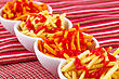 Potato Chips With Ketchup Isolated On Colorful Tablecloth stock photo