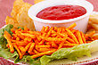Potato Chips, Red Sauce And Lettuce Leaf On Colorful Tablecloth stock photo