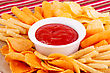Potato, Corn Chips In Bowl And Red Sauce On Colorful Tablecloth stock image