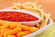 Potato, Corn Chips In Bowl And Red Sauce On Colorful Tablecloth stock photography