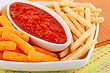 Potato, Corn Chips In Bowl And Red Sauce On Colorful Tablecloth stock photo