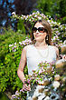 Pretty Blond Woman In Sunglasses Posing Near Blooming Tree