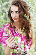 Pretty Curly Lady Wearing Pink Dress Touching The Branch Of Flowering Tree stock photo
