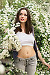 Pretty Slim Brunette Wearing Top And Jeans Posing In Flowering Bushes stock photo