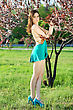 Pretty Slim Leggy Woman Wearing Turquoise Dress And Shoes Touching Leaves Of The Tree