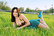 Playful Pretty Smiling Young Lady In Turquoise Dress And Shoes Lying On The Green Grass stock photo