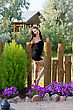 Pretty Young Woman In Black Dress Near The Wooden Fence stock photo