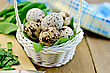 Quail Eggs In A White Wicker Basket With Sorrel, A Napkin On The Background Of Wooden Boards