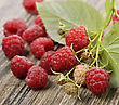 Raspberries With Leaves On The Rusty Wooden Table