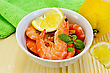 Raw Shrimp In A White Bowl With Lemon, Basil And Green Cloth On A Wooden Board stock photo