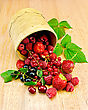Red And Black Currants, Raspberries, Strawberries, Cherries With Green Leaves In A Bowl From Birch Bark On A Wooden Board stock photo