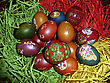 Red, Green, Blue, Yellow Easter Eggs In Paper Nest stock photo