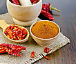 Red Pepper Powder In A Wooden Bowl Of Dry Cereal And Pods Of Red Pepper In A Mortar And A Wooden Spoon, Sacking On A Wooden Board stock photography