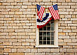 Red, White And Blue Bunting And Crossed American Flags Adorn A Casement Style Window Set In A Standstone Block Wall stock image