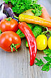 Red And Yellow Tomatoes, Sweet And Hot Peppers, Cucumbers, Potatoes, Carrots And Parsley On A Wooden Boards Background
