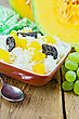 Rice With Caramelized Pumpkin, Prunes In A Clay Bowl, Raw Sliced Pumpkin, Green Napkin, Grapes On A Wooden Board
