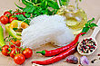 Rice Noodles Thin, Tomatoes, Peppers, Chopsticks, Garlic, Basil, Vegetable Oil On A Background Of Sack Cloth stock photo