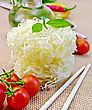 Rice Noodles Twisted, Tomatoes, Different Pepper, Oil In Carafe, Chopsticks On A Background Of Sack Cloth stock photography