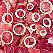 Pork Rings Of White Onion On A Background Of Red Pieces Of Meat (texture stock image