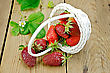 Ripe Red Strawberries Poured From A White Wicker Basket, Flowers And Strawberry Leaves On The Background Of Wooden Boards stock image