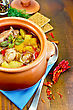 Roast With Chicken Meat, Potatoes And Peppers In A Clay Pot, Napkin, Spoon, Crispbreads, Dill On A Wooden Board stock photo