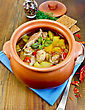 Roast With Chicken Meat, Potatoes And Red Pepper In A Clay Pot, Blue Napkin, Spoon, Crispbreads, Dill And Pepper In A Jar On A Wooden Board stock image