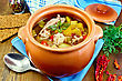Roast With Chicken Meat, Potatoes And Red Pepper In A Clay Pot, Blue Napkin, Spoon, Crispbreads, Dill And Pepper In A Jar On The Board