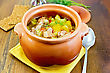 Roast With Chicken And Potatoes In A Clay Pot, A Yellow Napkin, Spoon, Crispbread, Pepper In The Pot On A Board
