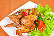 Roasted Chicken Wings Garnished With Fresh Green Salad, Pepper And Greens stock photo