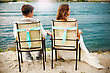 Romantic Young Newlyweds Couple Sitting Near River Or Lake On The Beach, Resting After Wedding Ceremony. Back View Of A Couple stock photography