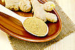 Asian Food  Roots Of Fresh Ginger, A Wooden Spoon With A Powder Of Ginger On Pottery On A Napkin On A Burlap Background Wooden Board stock photo
