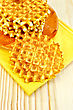Round Golden Waffles On A Plate And A Yellow Napkin On A Background Of Wooden Board